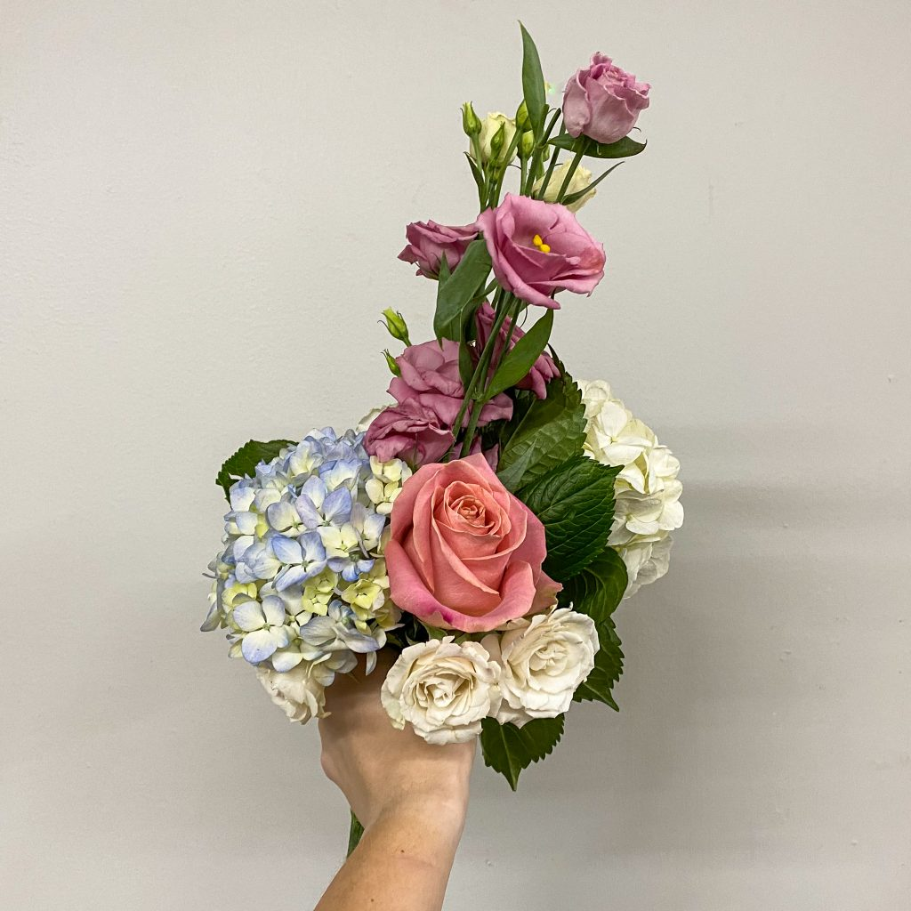 Hand holding bouquet of pink and white flowers