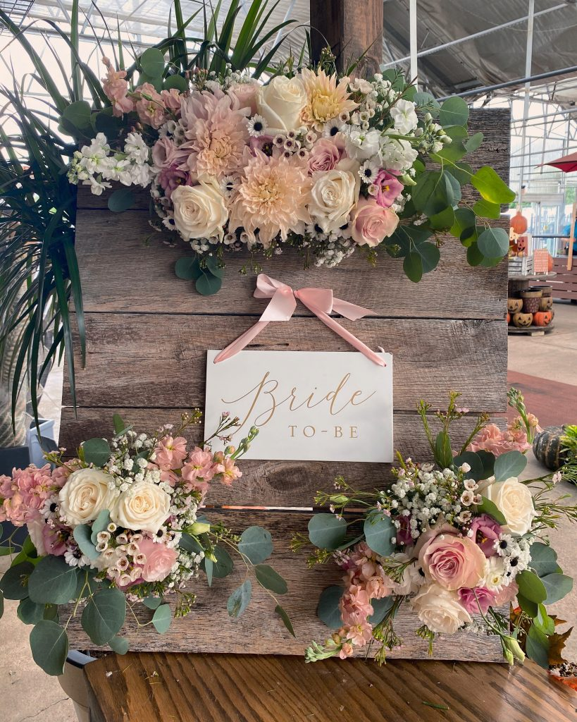 """""""Bride To Be"""" sign on wooden board decorated with pink and white flowers"""